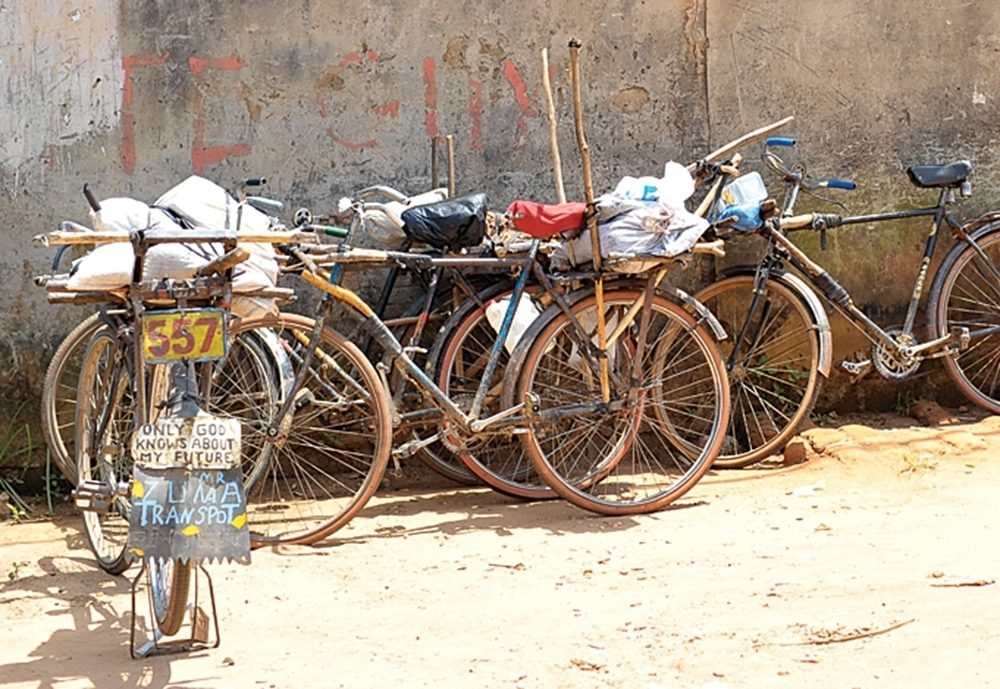 Bikes are lined up along the wall of a building in Chishiko, Zambia