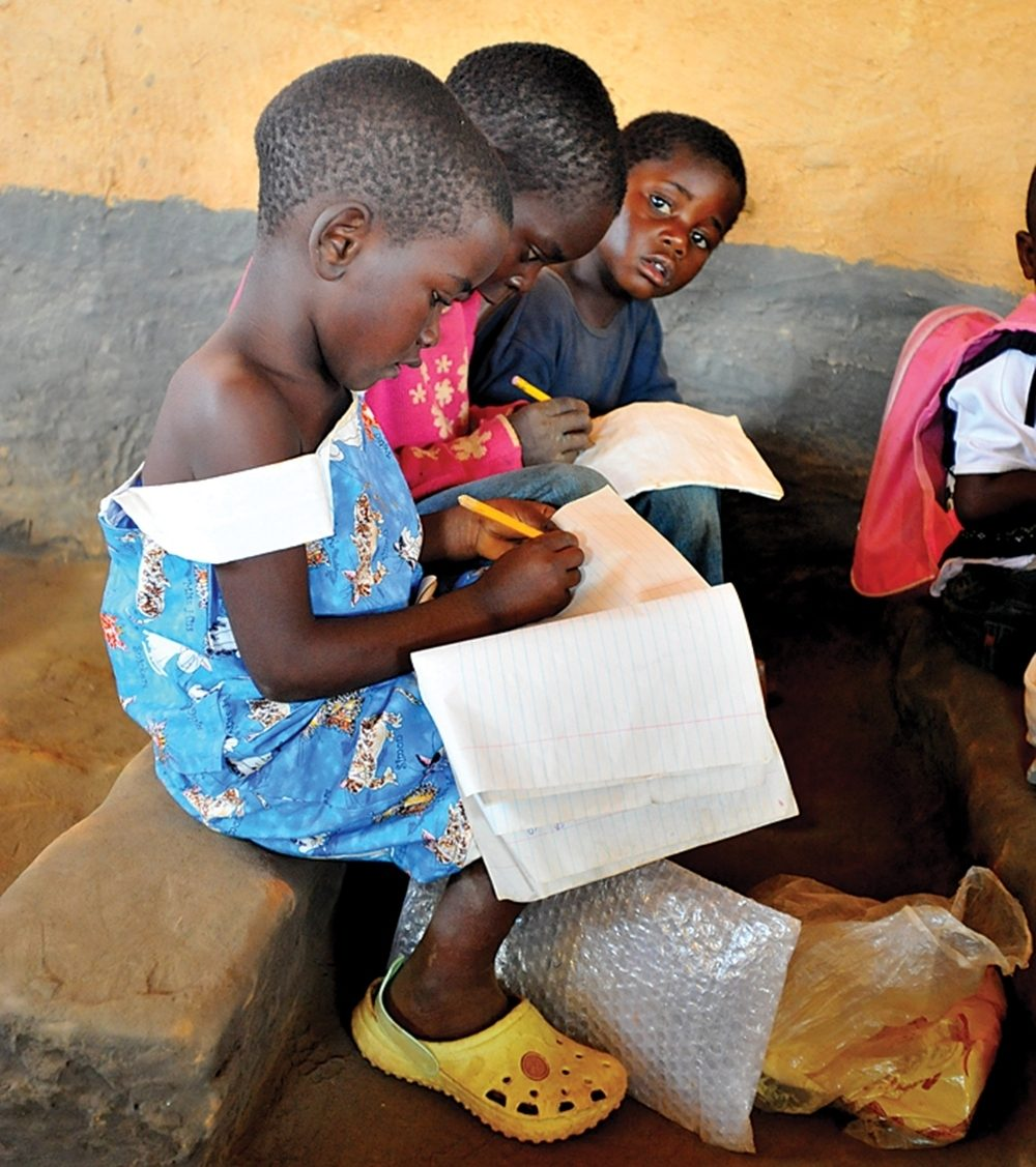 Children study at a school Chishiko, Zambia, where the mud brick building with a dirt floor serves 120 students.