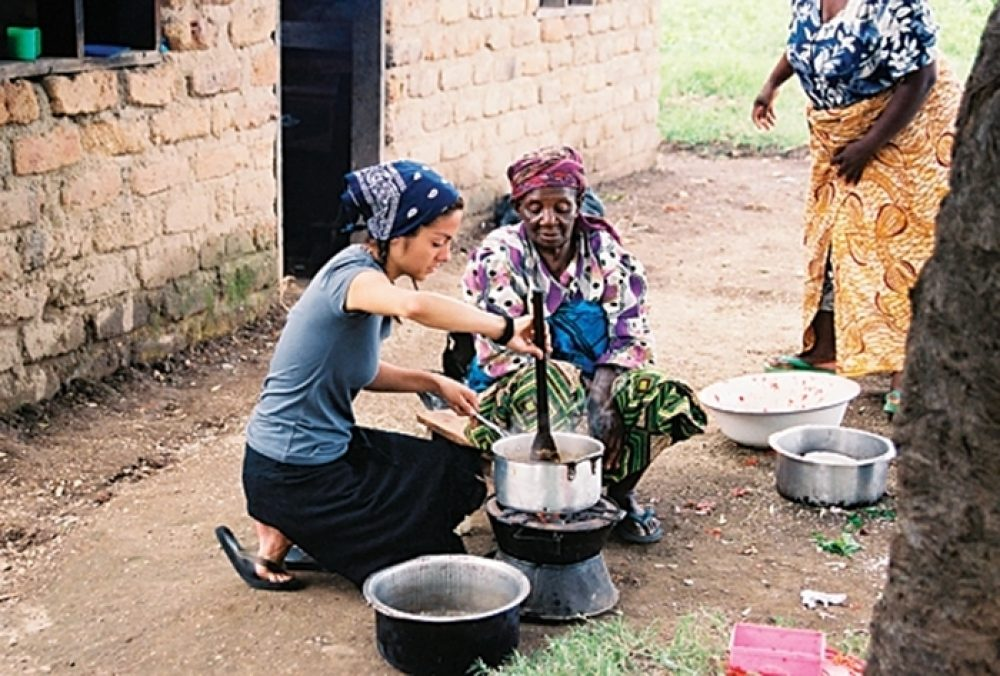 Aby Nelms helps a woman cook over an outdoor stove in Chishiko, Zambia.