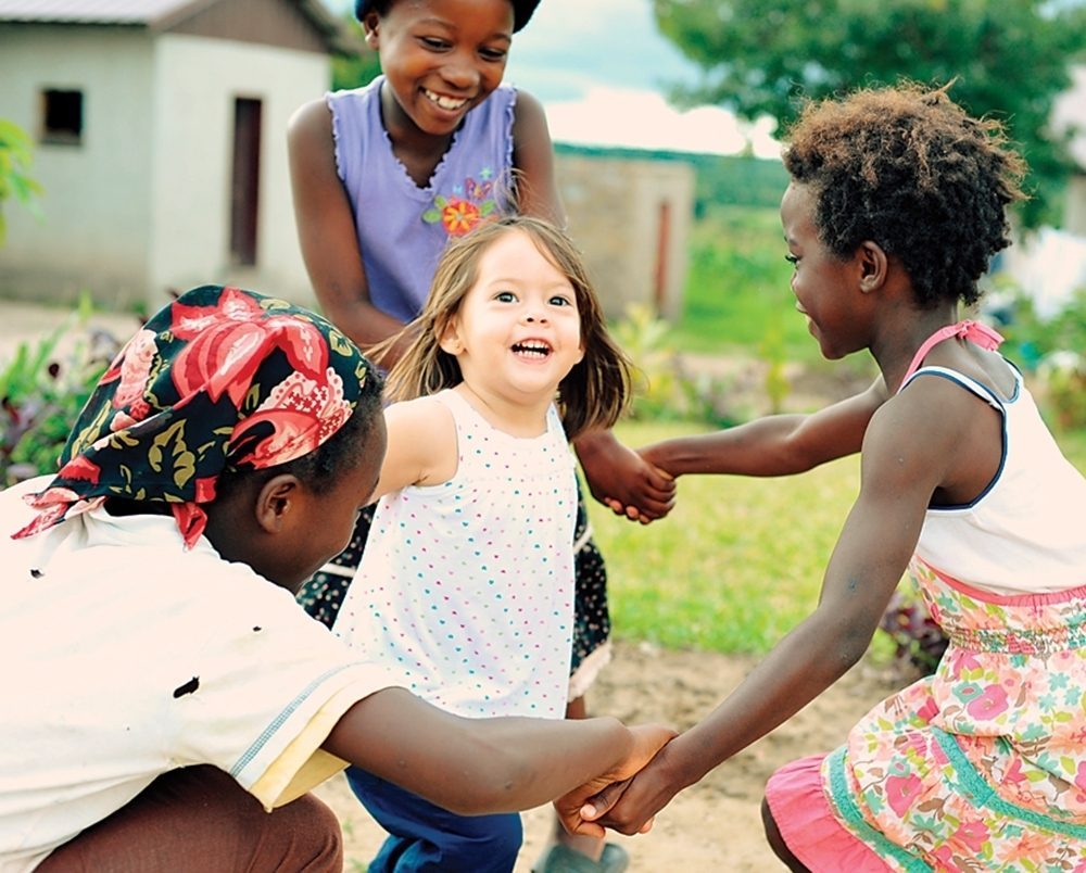 The child of American missionaries plays with local children in Chishiko, Zambia.