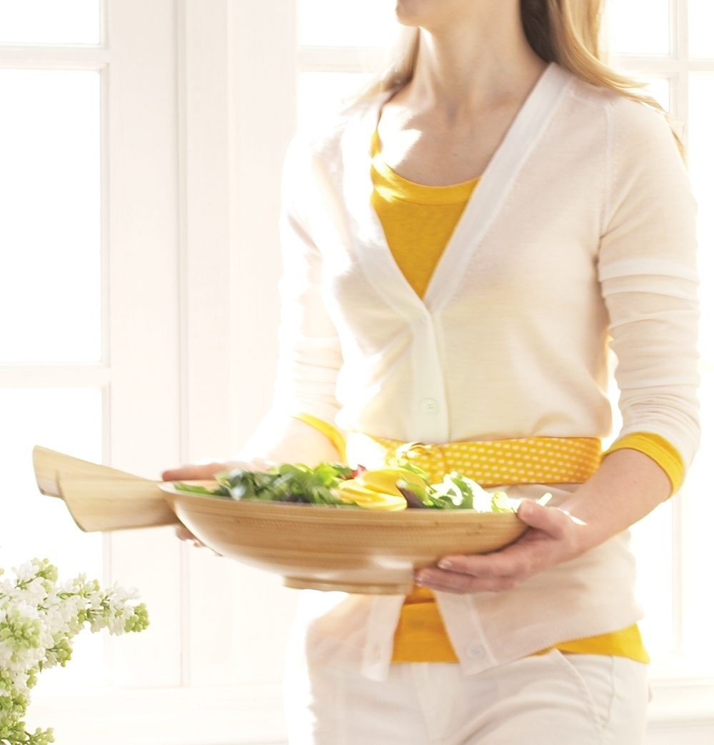 A woman holds tongs and a wooden bowl filled with salad.