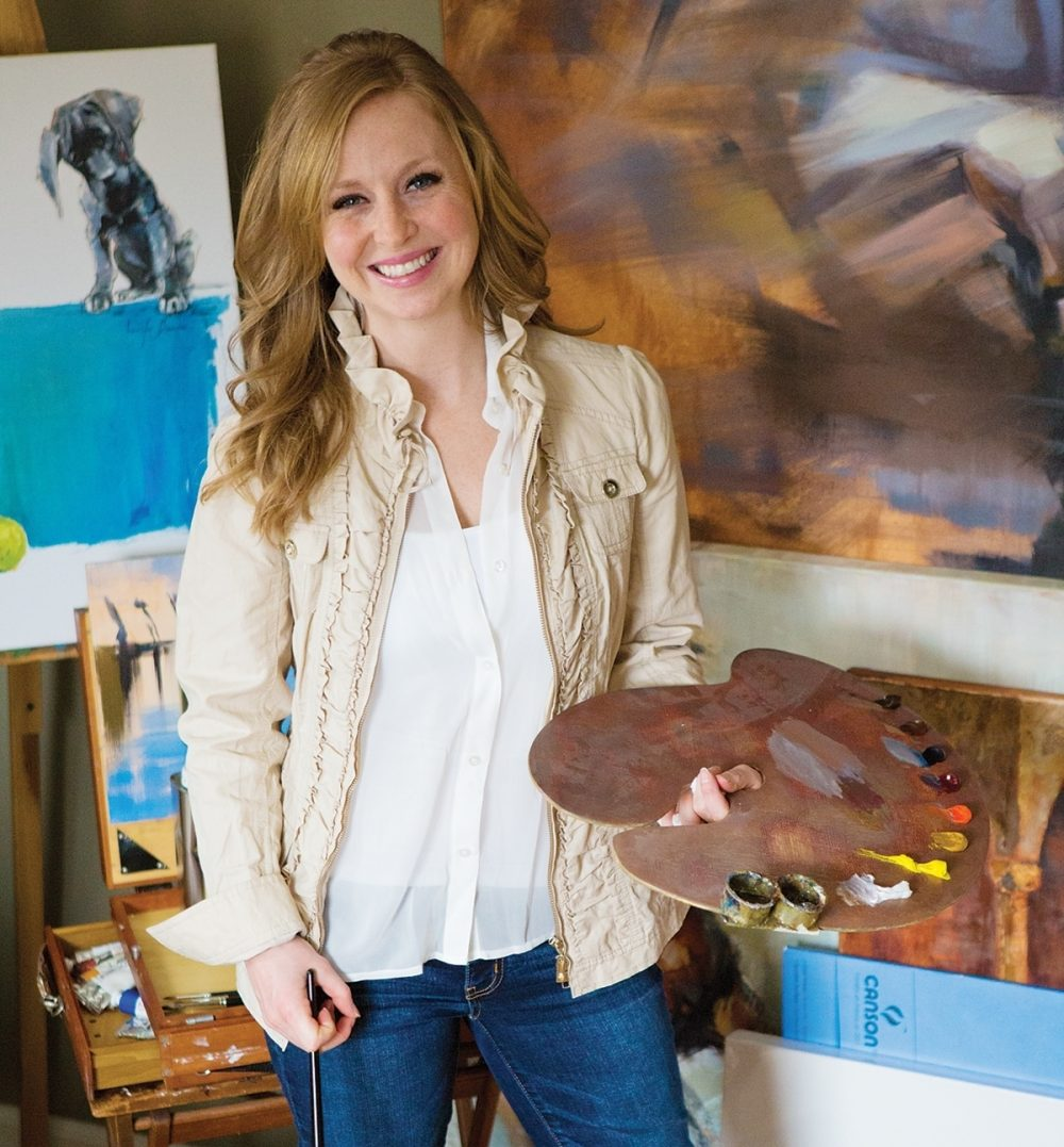 Jennifer Brandon, an illustrator for Lamplighter Publishing, holds a palette and brush in her studio.