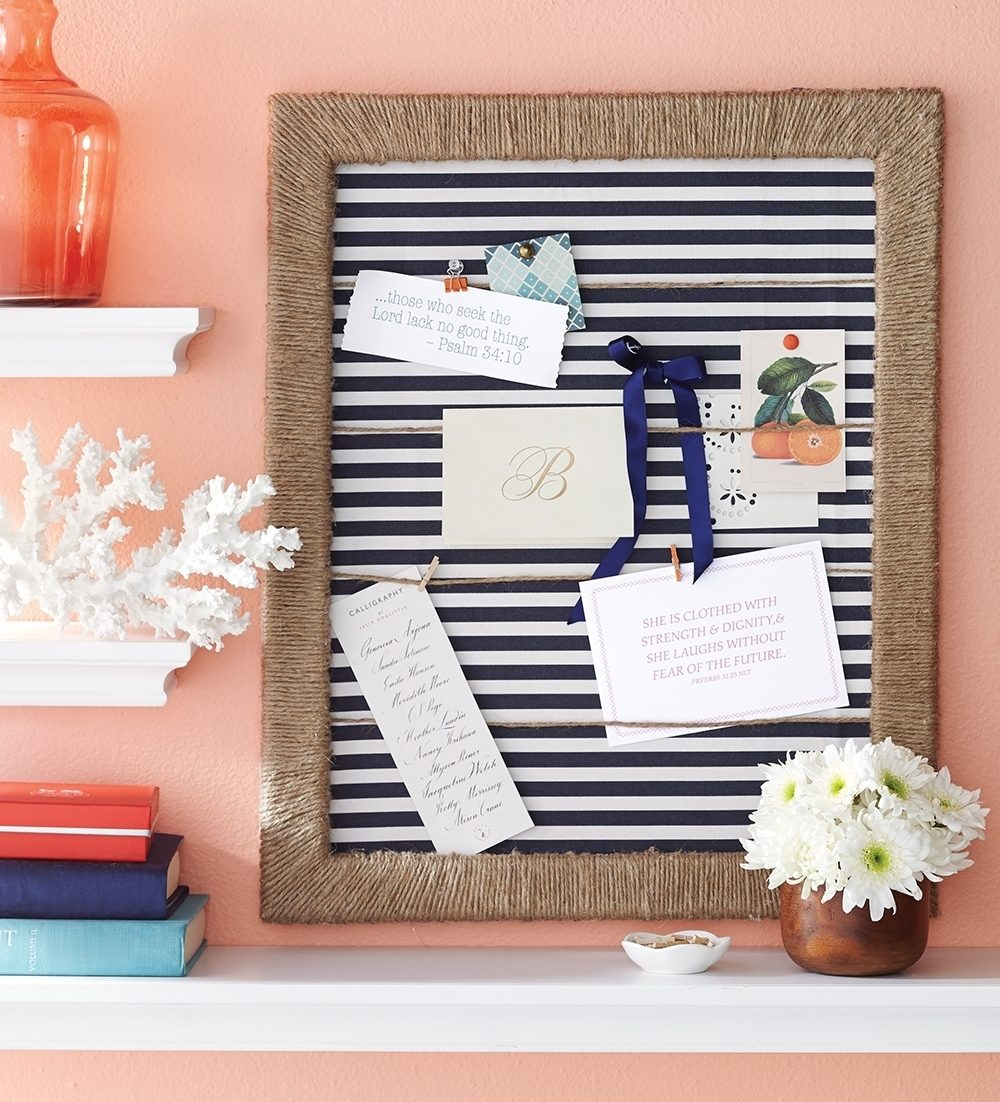 This Jute Frame Board uses 1 to 2 spools of jute wound tightly around an empty frame to create texture. Horizontal jute strands glued to the inside of the frame repeat the design element and provide a place to hang notes. Ribbon, raffia, leather strips, string and dozens of other materials would work equally well, transforming the look and feel. A striped fabric-covered cork board adds visual contrast against the solid colored wall.