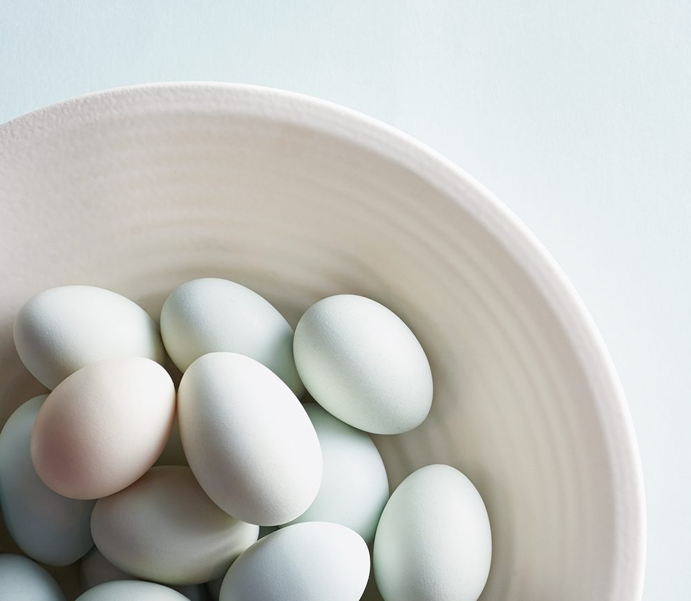 Multi-colored pastel eggs rest in a bowl