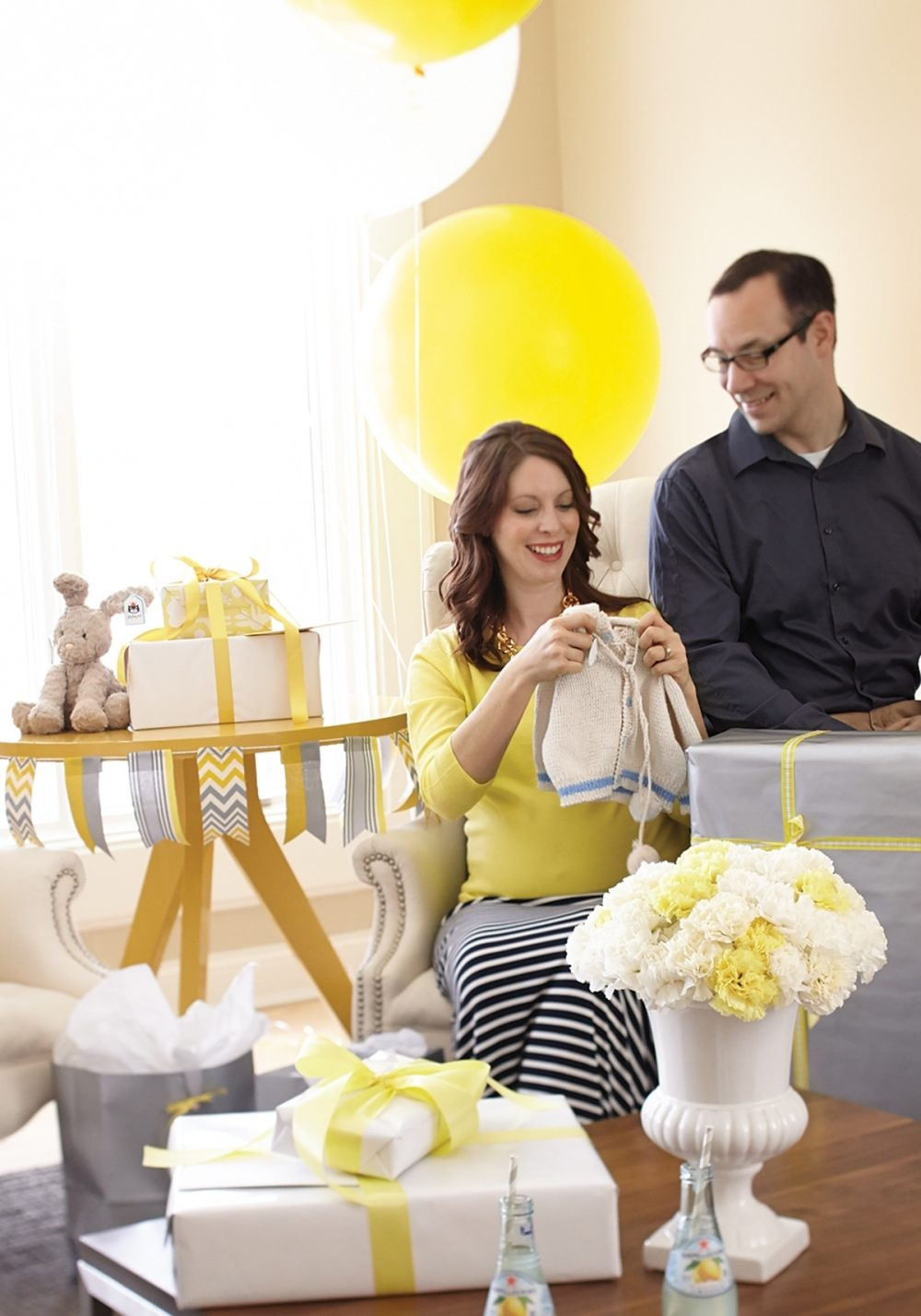 A husband and wife unwrap a sweater at a co-ed baby shower