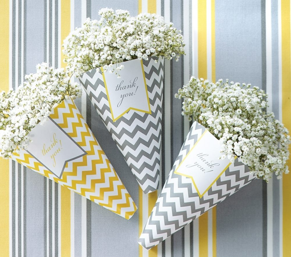 Paper cones in yellow and gray with baby's breath and a note of thanks make easy and thoughtful baby shower favors.