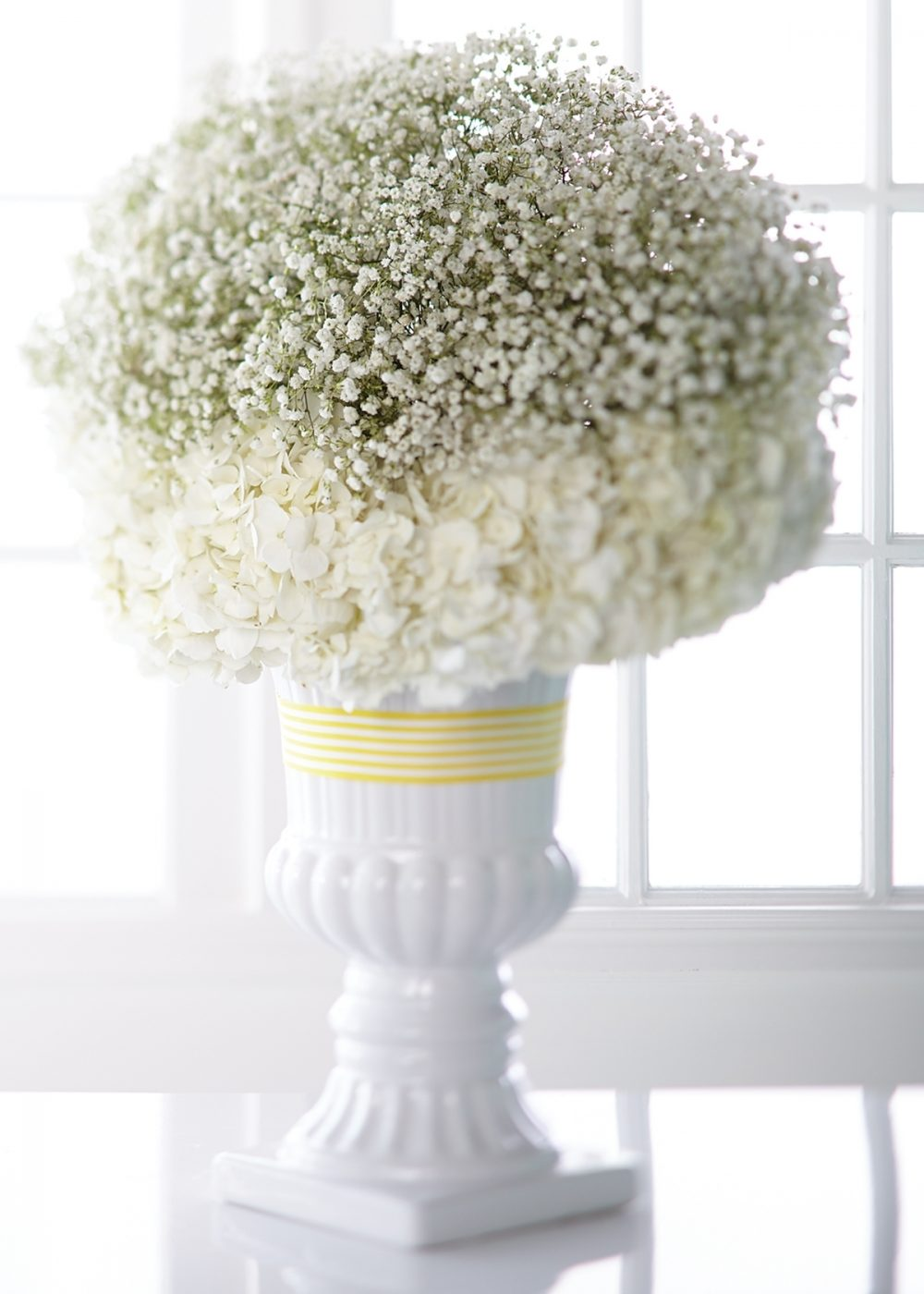 A bouquet of white baby's breath and hydrangeas in a white urn is a flower arrangement that works well with any baby shower theme