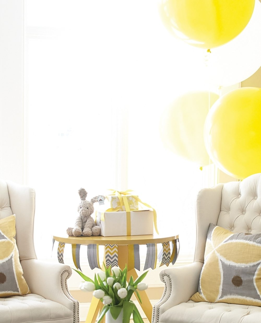 A neutral living room is decorated for a co-ed baby shower with yellow and white balloons and yellow and gray ribbons and pillows