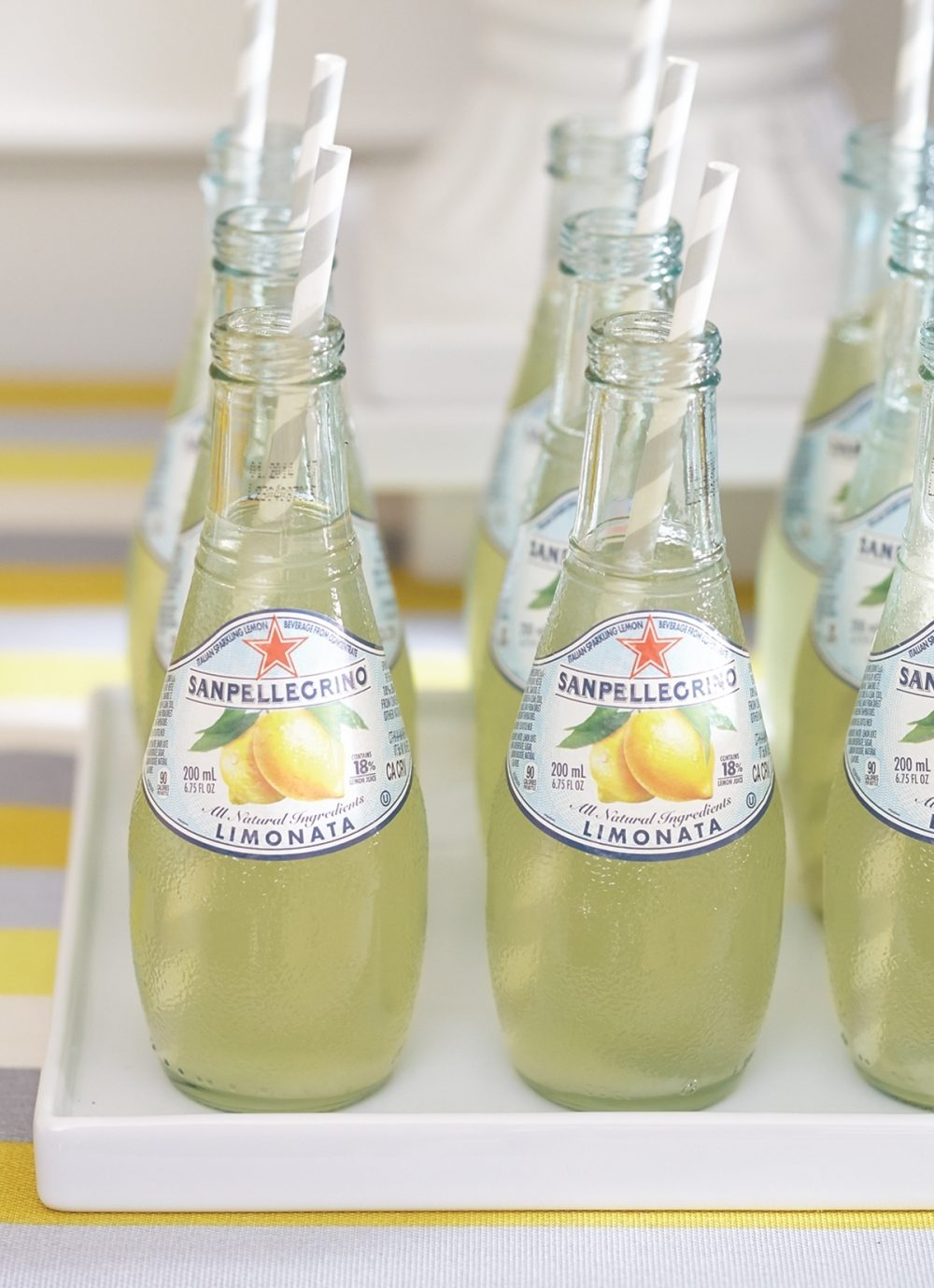 Bottles of Sanpellegrino Limonata with straws at a yellow-and-gray themed co-ed baby shower