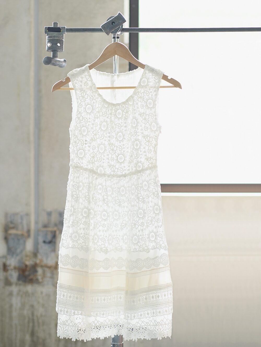 A white lace dress waits on a hanger.