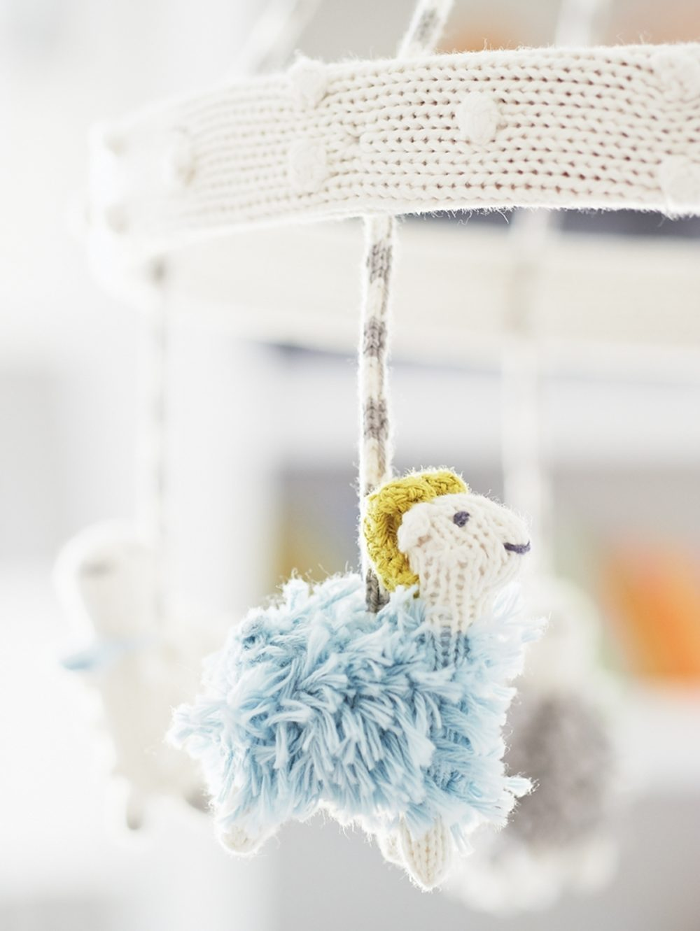 Knitted animals dangle from a baby's mobile.