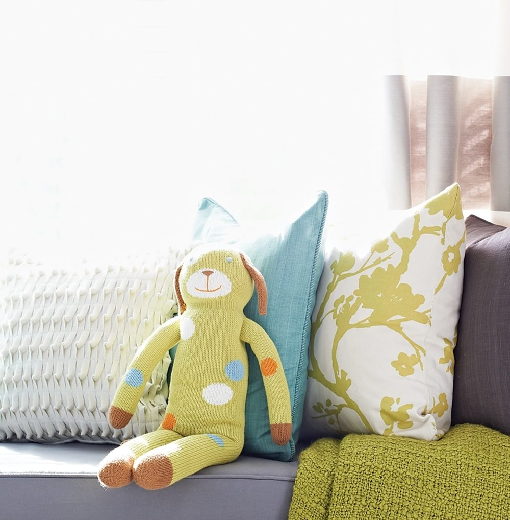 A knitted dog rests on a window seat with pillows in a baby's nursery.