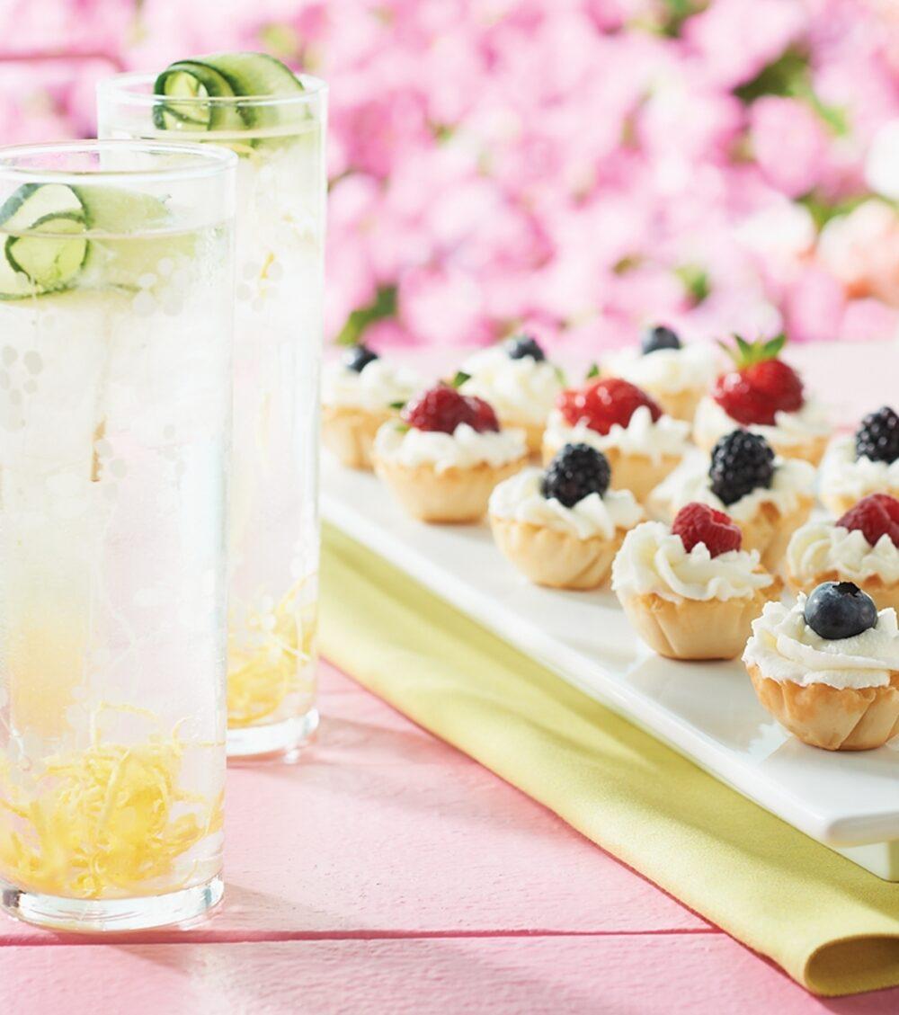 Small Berry Tarts are served on a white platter alongside Lemony Cuke Zesters.