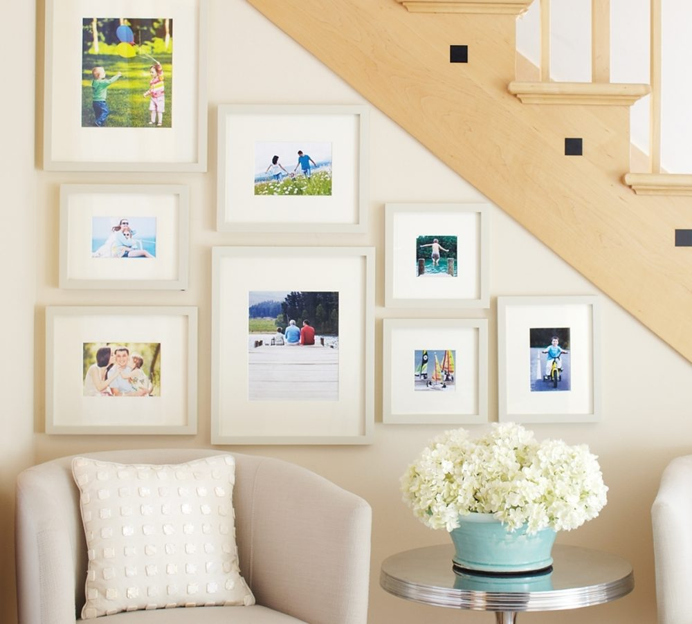Filling a wall with closely spaced frames creates a wallpaper effect. A photo grouping can even be hung filling a space entirely, wall to wall, floor to ceiling. If some photos are slightly obscured, heighten their impact by pulling away a chair or the edge of drapery.