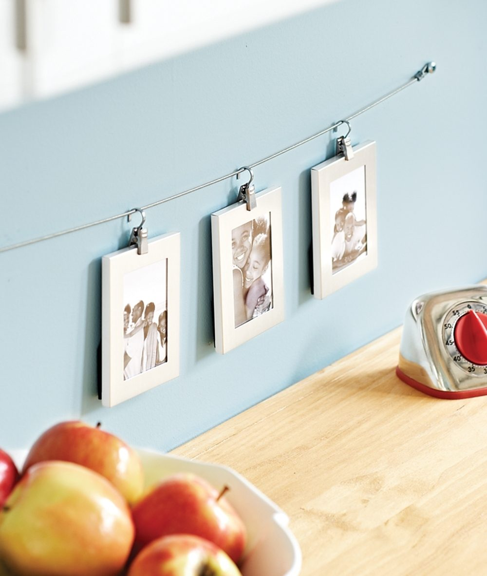 Purchased clips hang small photo frames from a wire.