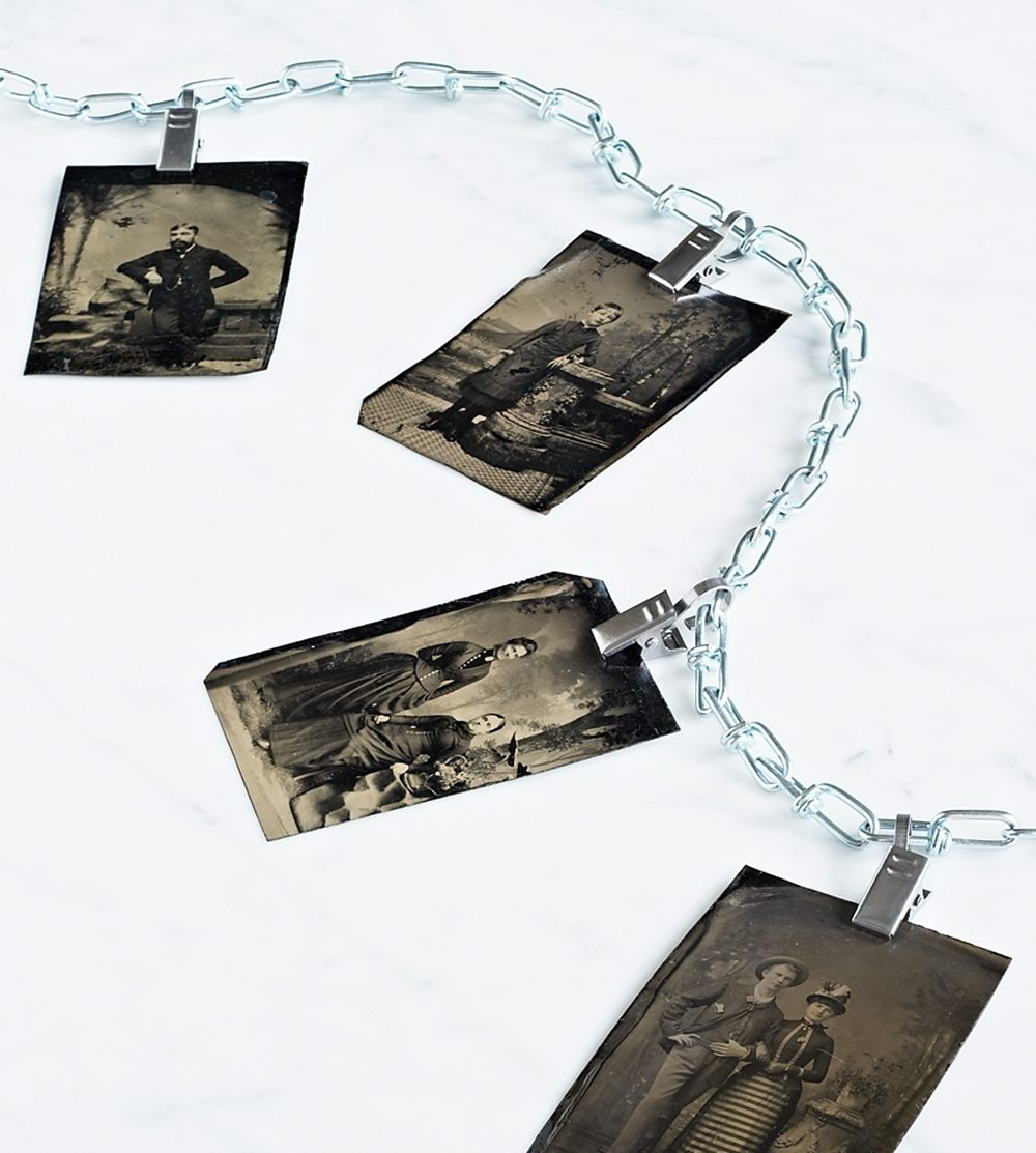 Vintage tintype photos are clipped to a chain.