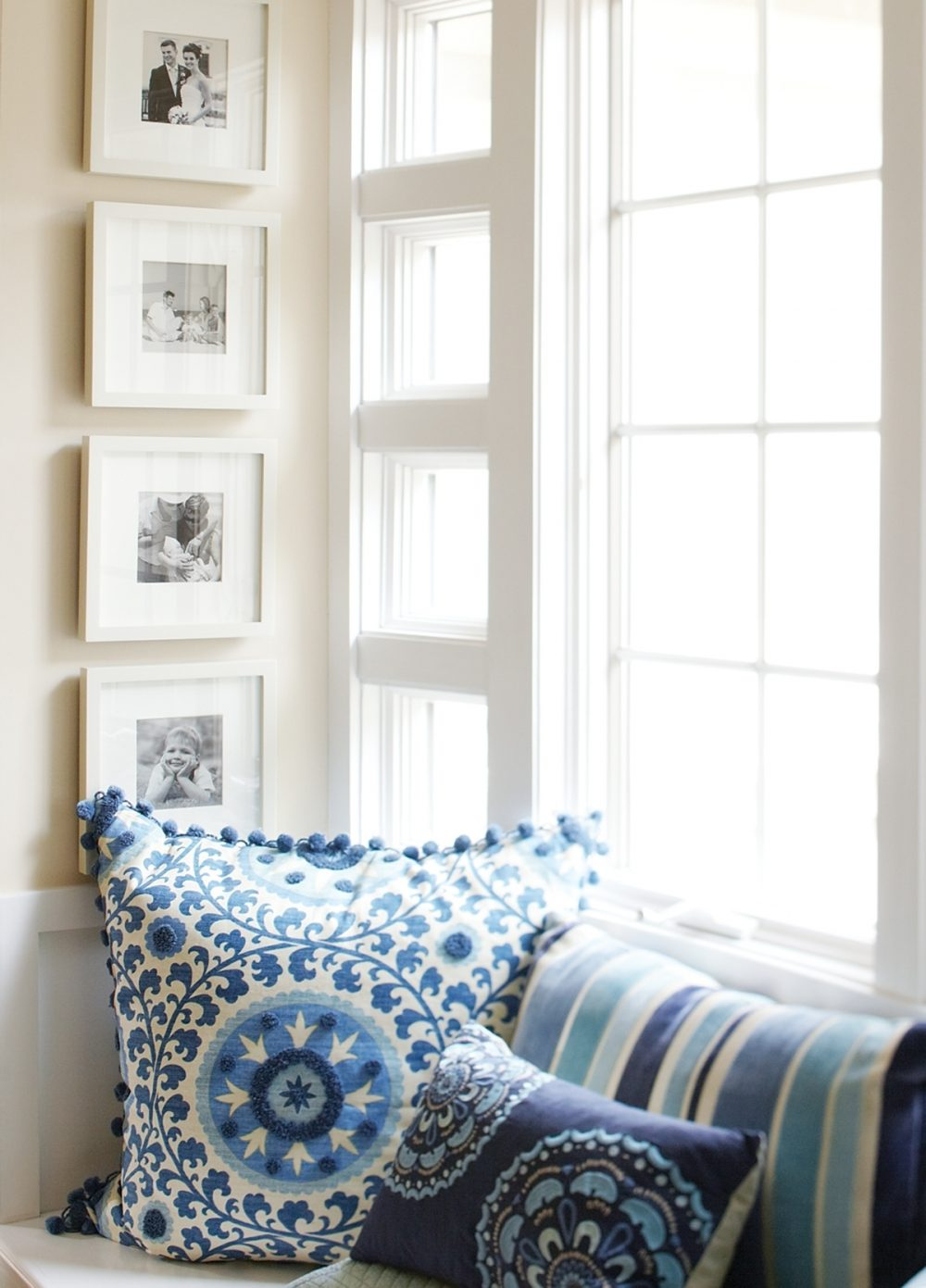 A gallery wall is downsized to fit a window seat alcove.