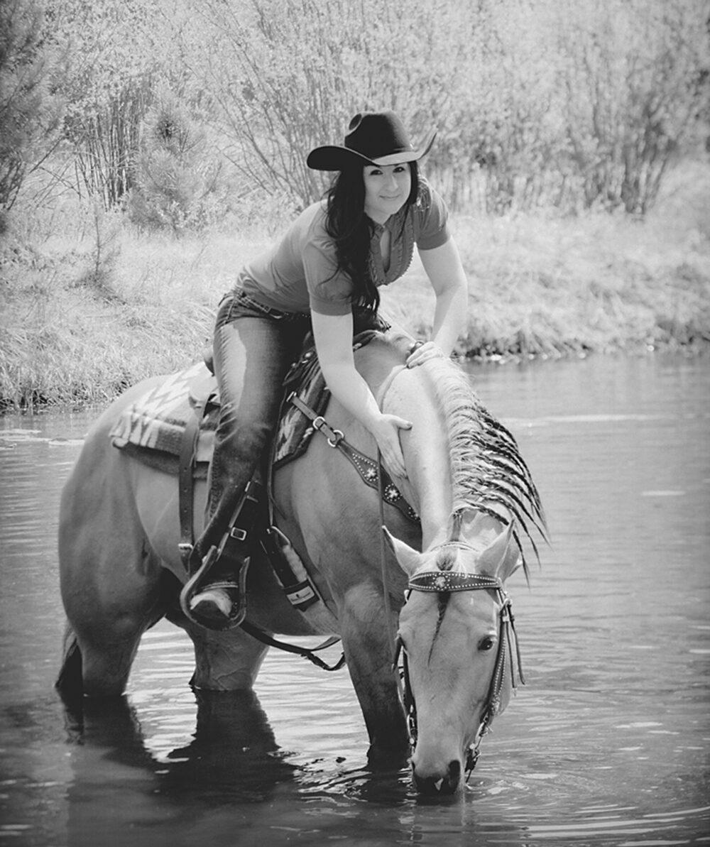 Sara Weaver, a survivor of the Ruby Ridge standoff, rides a horse through a river.