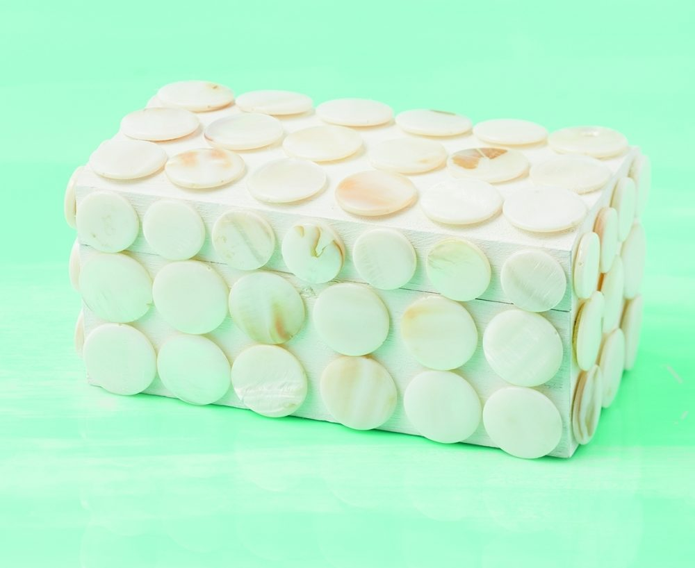 To encrust this DIY box with mother-of-pearl, cover surfaces with evenly placed disks using a high temp hot glue.