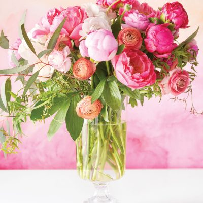 Peonies, Ranunculus, Ivy & Snow Gum Eucalyptus in a footed glass vase