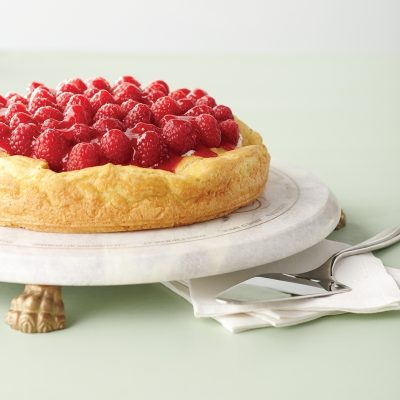 A light-as-air cream puff cake topped with white chocolate provides a soft landing for luscious raspberry fluff. The unmatchable flavor and deep hue of raspberries counter the richness of sweetened whipped cream.