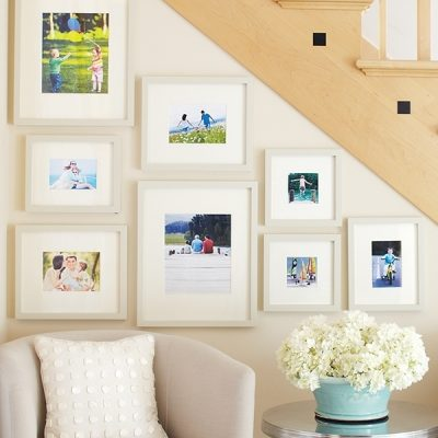 A gallery wall displays photos in the space under a staircase.