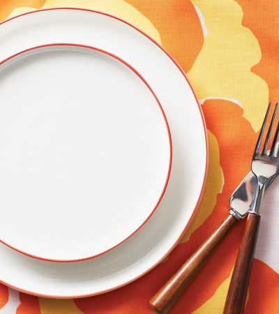 A summer place setting with white plates and orange and yellow linens