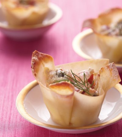 Baked wonton cups cradle bite-sized tastes of savory smoked salmon. Display these beauties on trays set out for guests to help themselves or on pretty individual dishes.