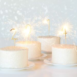 Sparkling candles spell out the new year on small cakes