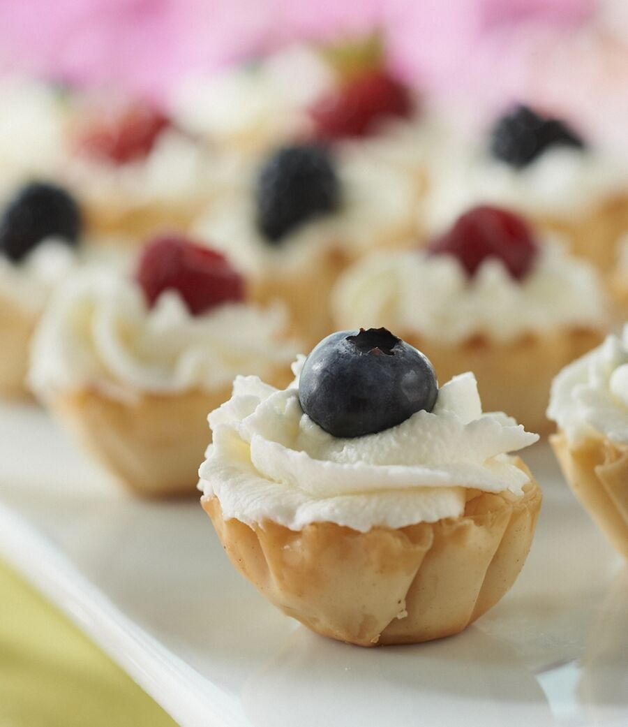 Berry Tarts are filled with a mix of yogurt, whipped topping and heavy whipping cream, then topped with assorted berries.