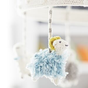 Plush animals dangle from a baby's mobile.