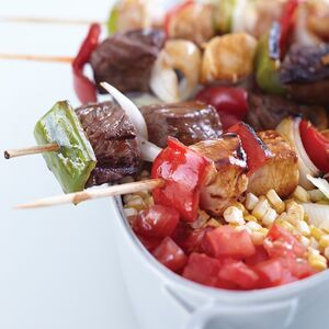 Skewers of marinated chicken, steak, and vegetables are easy for guests to handle at a casual al fresco dinner.