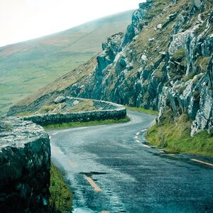 A narrow road winds through rocky hills in the Dingle Peninsula in Ireland.