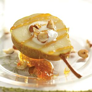 A roasted pear is served with vanilla yogurt, hazelnuts and a drizzled ginger-agave sauce.