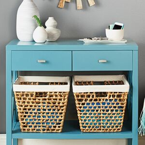 An entryway with a turquoise table holds baskets and incident items
