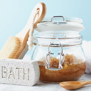 A DIY scrub made with sugar or salt in a glass container with bath tools