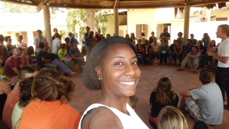 Black Woman Peace Corps Volunteer smiles for the camera with her trainee group sitting in a circle in Senegal.