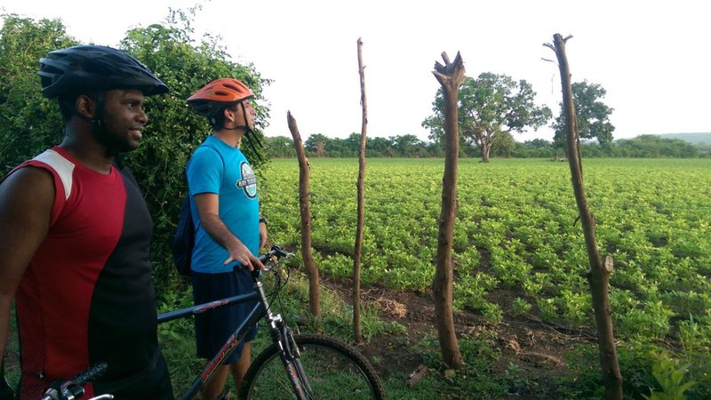 A Latinx Peace Corps Volunteer and a Dominican man stand holding on to mountain bikes. Each is wearing a helmet.