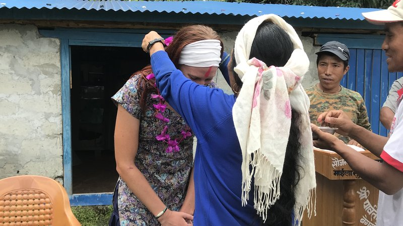A female Volunteer receives a blessing in the form of a flower necklace from her Nepali host mother.