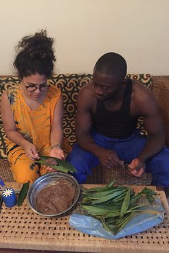 A Puerto Rican woman and Cameroonian man sit on a couch, cooking together