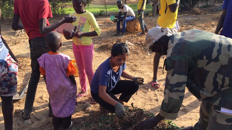 An American woman digs in the dirt with her fellow Senegalese friends