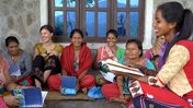 Several Nepalese women and one American volunteer, all in colorful clothing, sit together on a porch reading and smiling.
