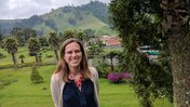 Kait at Decaf Facility in Colombia. She is outside and there are green mountains in the background.