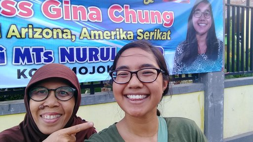 An Asian-American female Volunteer stands next to her Indonesian host mom and smiles in front of a banner with her face on it