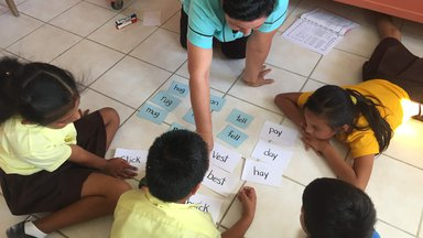One teacher and four students in a circle looking at cards with words on them