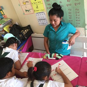One teacher watching three students write