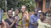 Health Volunteer Emma celebrates her return to Malawi with her community by dancing