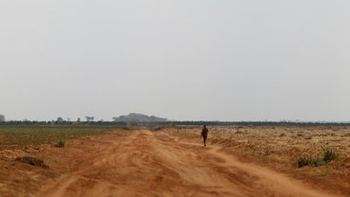 A bare dusty dirt road leads off into a flat, treeless land