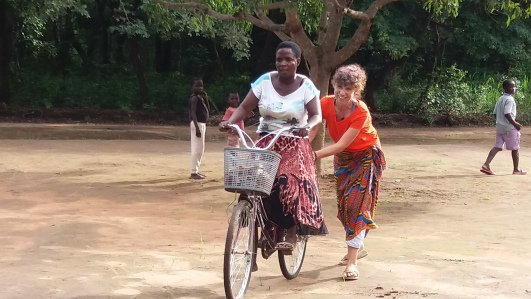 An older female Volunteer teaches a older Malawian female how to ride a bike
