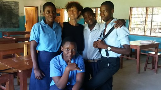 An older Volunteer stands with her Malawian high school students